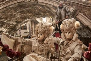 Gondolier and modelers under a Venetian bridge