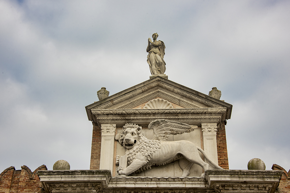 A closed book, symbolizing war, held by St. Mark's lion, the Arsenale